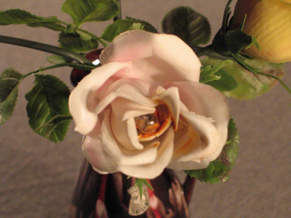 Lampe der foten er forma som ein vase med roser der det er sett små pærer i kvar av blomane. Slank konisk vase med hank og tut, oppi denne 2 raude, 2 rosa og 1 kvit plastrose. Kvit plastledning med bryar midt på, truleg sekundær