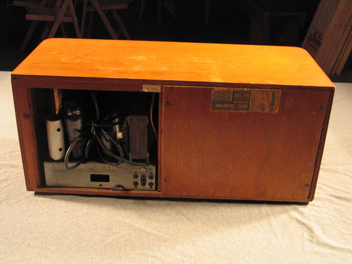 Radio med trechassis. Søkevindauge og høgtalar i front. Søkevindauget har halvrund stasjonsoversikt
