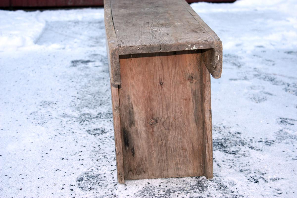 Benken er sett saman av to H-forma beinr, ei fjøl oppå til sete og to langsgåande fjøler på sidene til avstiving. Høvla profil på sidebord og bein.
