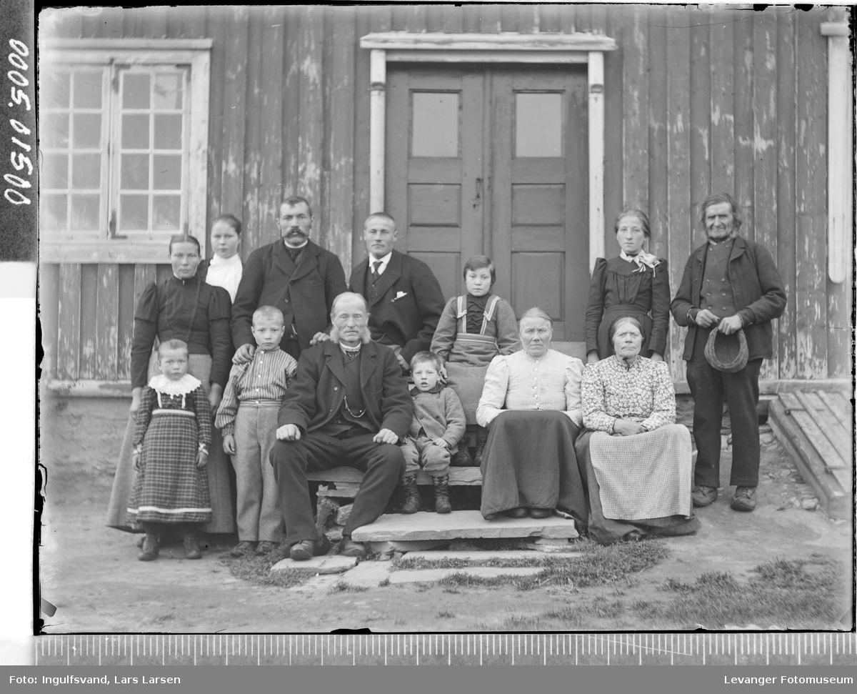 Gruppebilde av fire menn, fem kvinner og fire barn foran et inngangsparti.