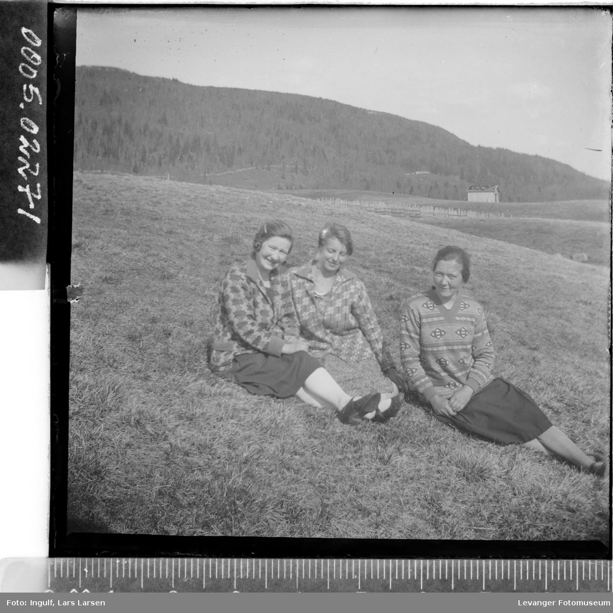 Gruppebilde av tre sittende unge kvinner.