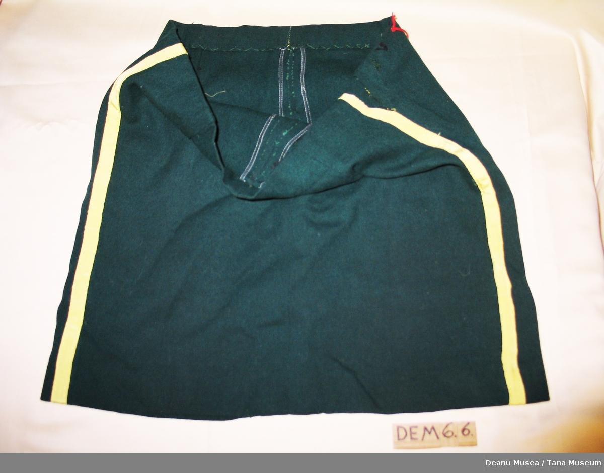 Skjørtet er sydd av mørkegrønt klede i ull med påsydde gule bånd i silke .