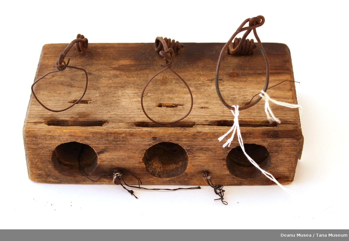 En trekloss med 3 hull inn mot midten fra siden og tre løkker av metalltråd festet på toppensettes i spenn nede i hullene hvor en utløser mekanisme slår ut å fanger musen.  Fellen er håndlaget.