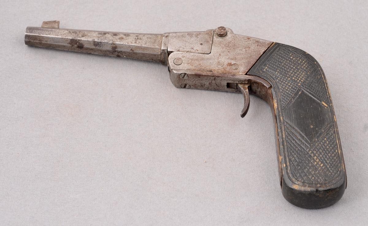 Enkel heimegjort pistol utan avtrekkarbøyle. Kaliber 22. Rifla løp. Siktemiddel skur og korn. Spennmekanisme ved at ein knekker pistolen, løyser ut ved å trykke på sidebolt. Skjefte i svartlakkert tre, truleg bjørk. Skoren rutemønster.