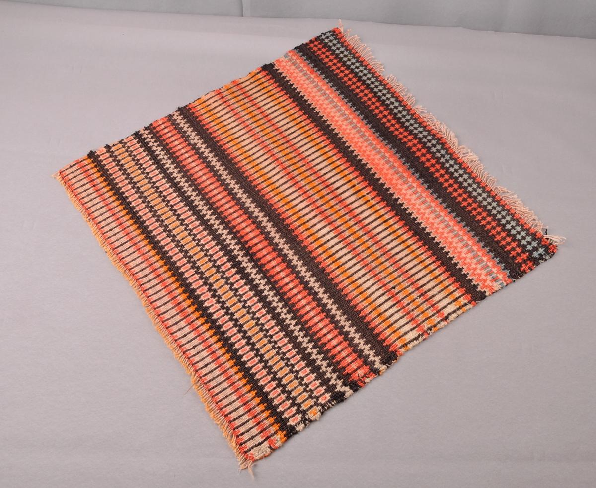 """Krokbragdteppe (enkel krok). Vove på 3 skaft. Teppet er kasta over med maskinsaum langs to av sidene. Frynser langs dei to andre. Renning av totråds ullgarn. Innslag av plantefarga ullgarn i raudt, blått, fiolett, orange, kvitt. Vevd medmotiv av """"kjevler"""" og krokbordar."""