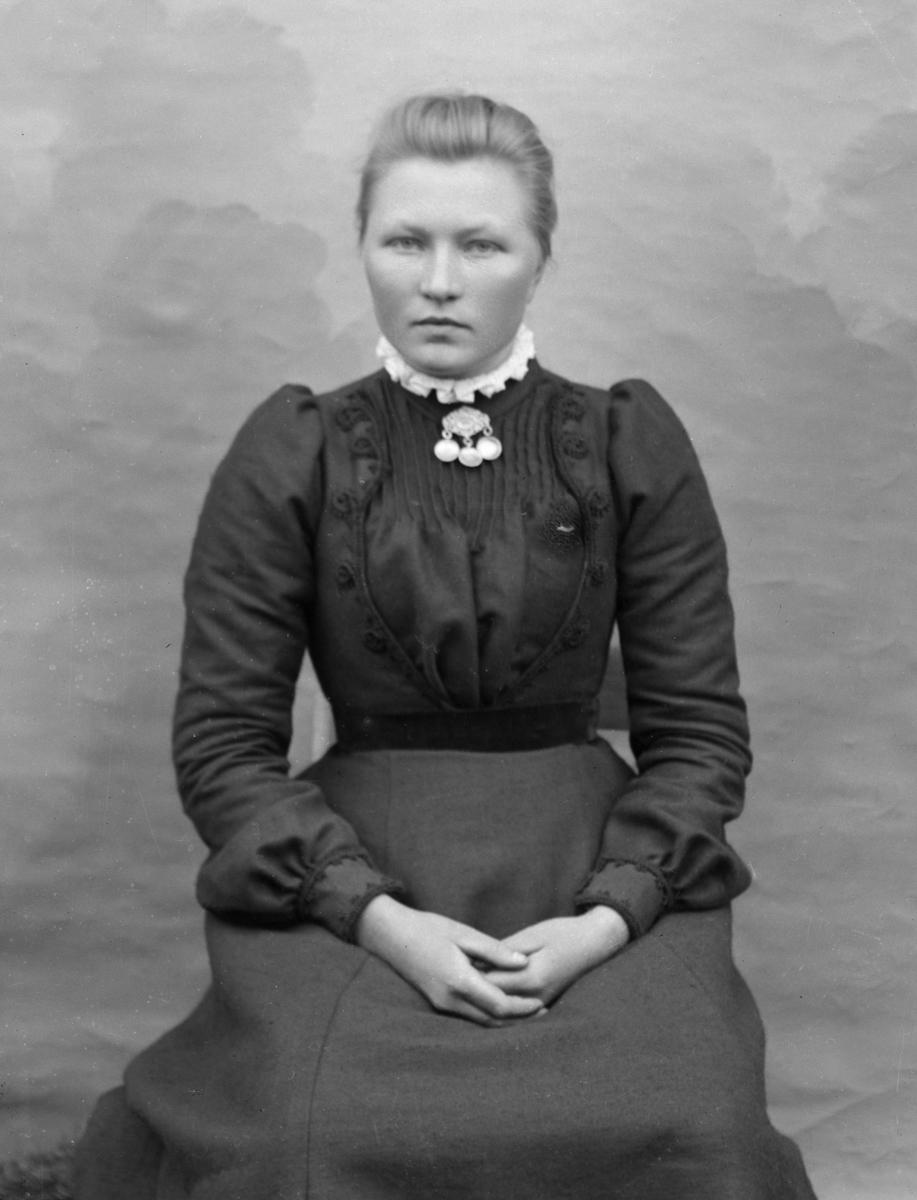 Kvinne i mørk kjole og sølje, sittende foran lerret