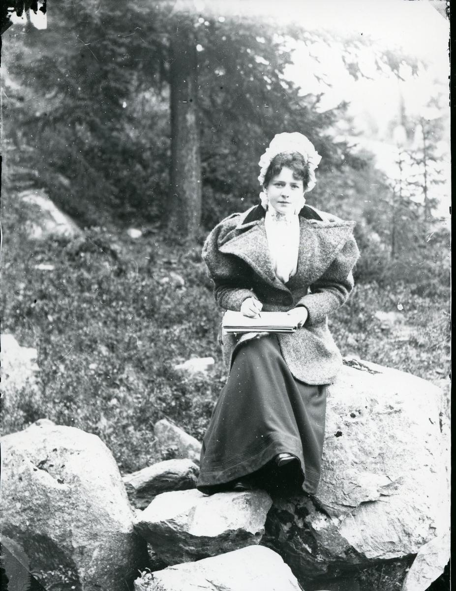 Kvinne sittende på stein, med bok e.l. på fanget, skog i bakgrunnen