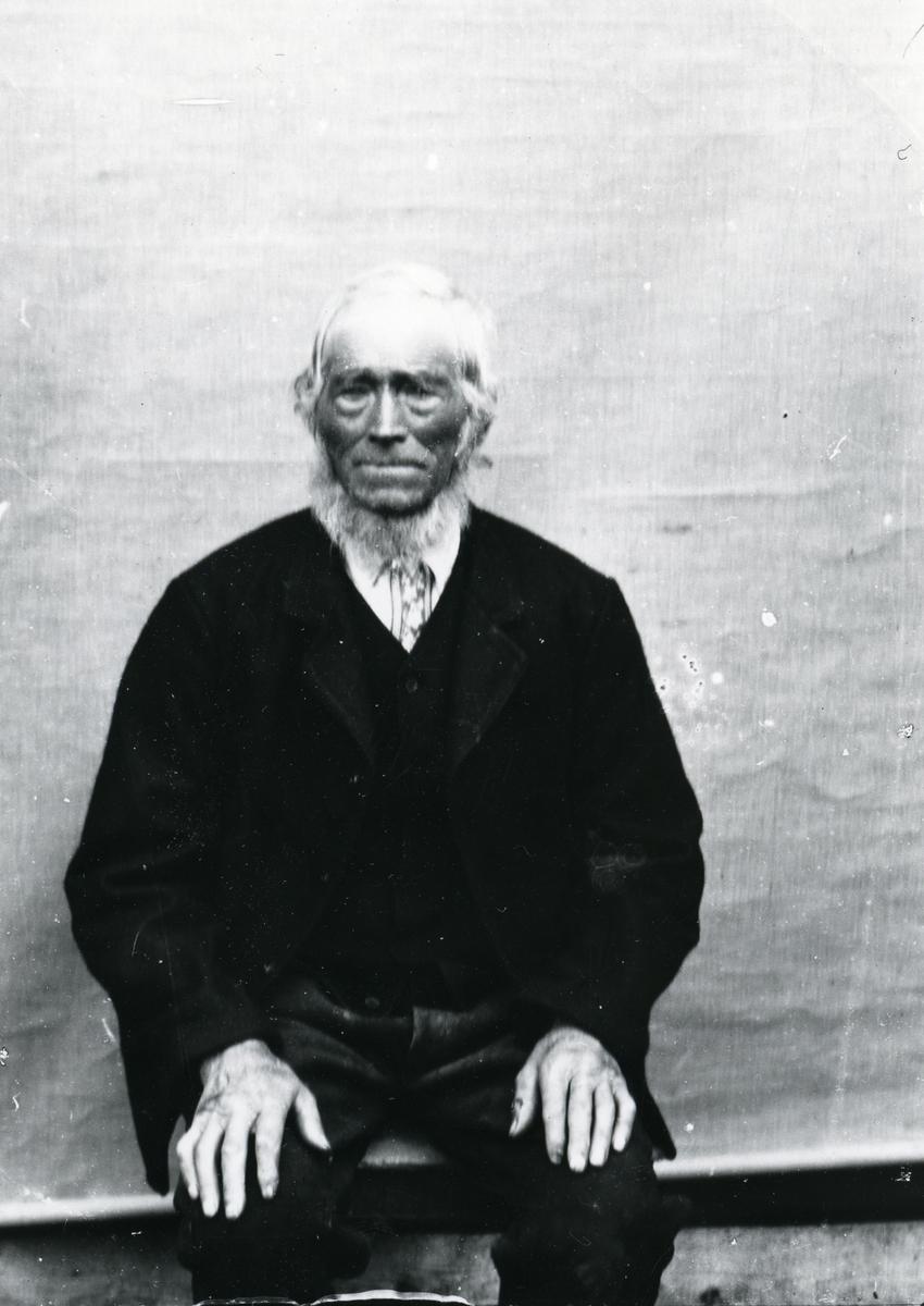 Eldre mann, sittende foran lerret