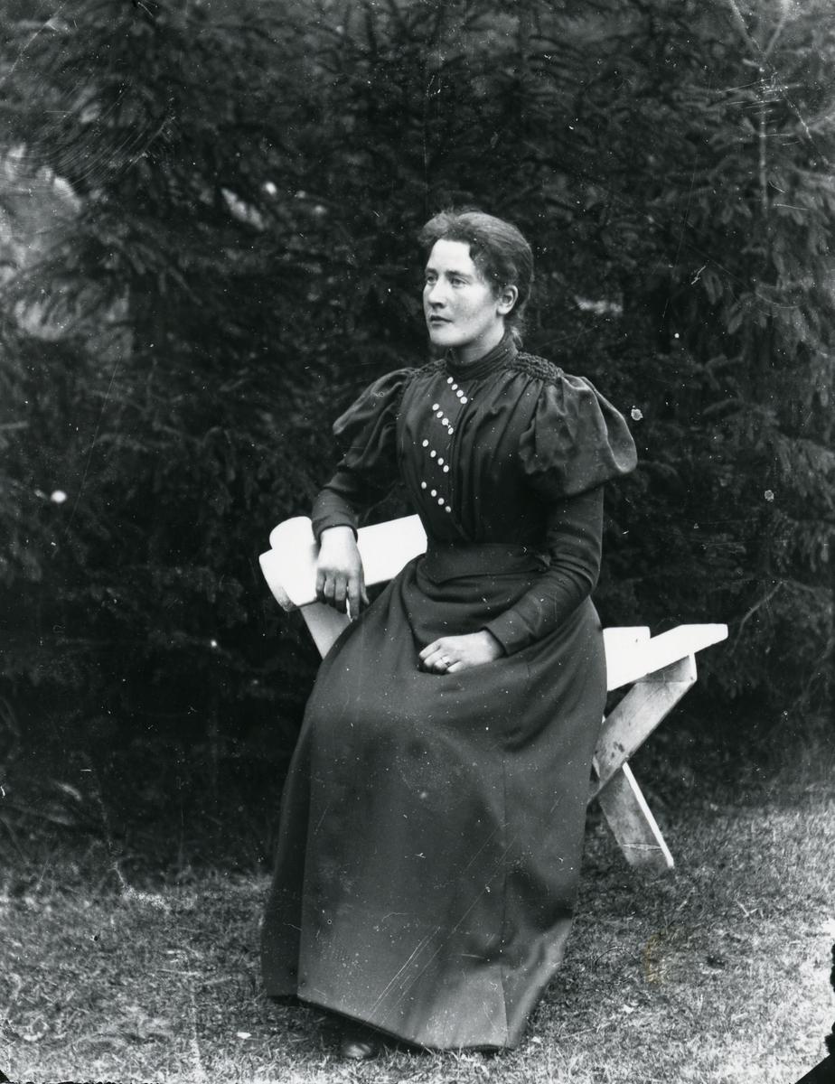 Kvinne på hvit benk, foran skog