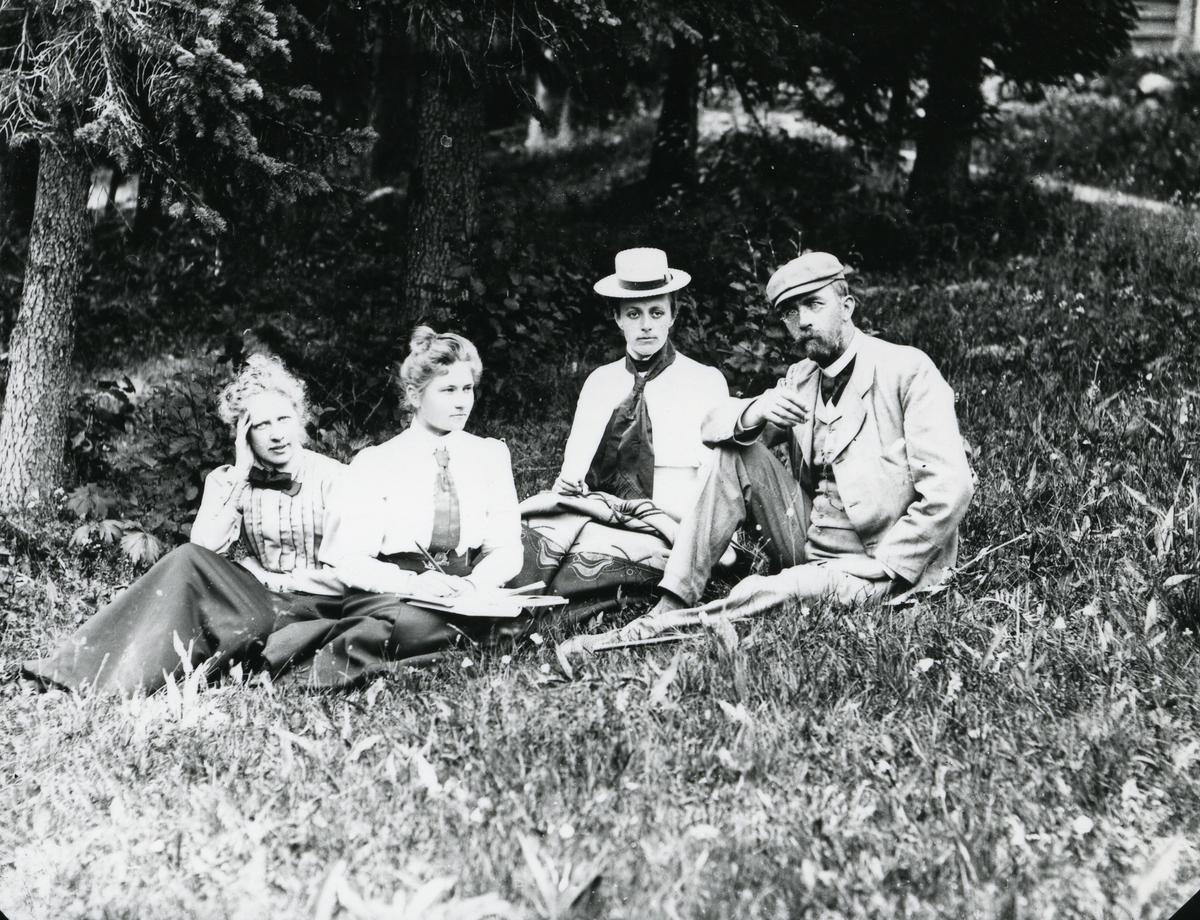 Mann og tre kvinner, sittende i gress foran skog og vei