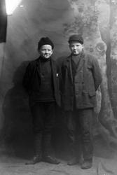 Studioportrett av to gutter i helfigur. De har sigaretter i