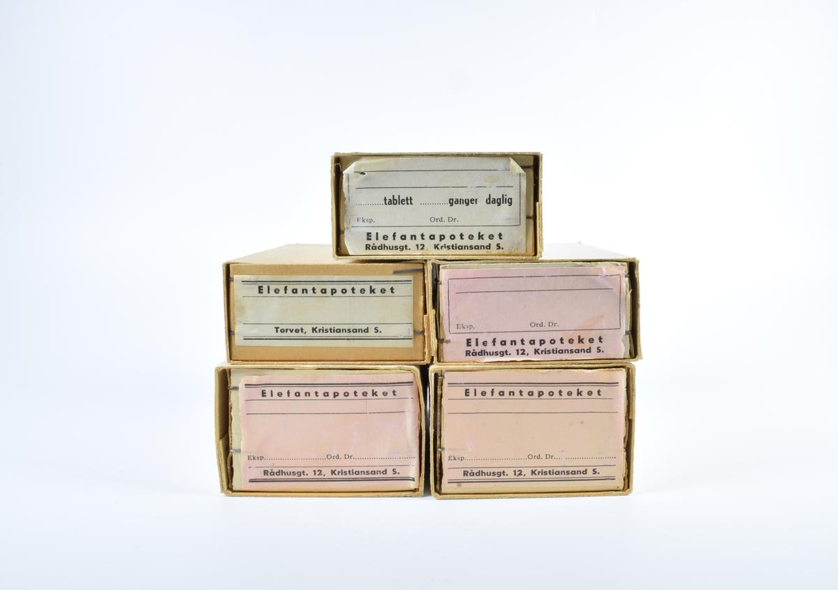 Fem rektangulære esker i papp med etiketter fra Elefantapoteket. Eskene består av to separate deler, hvor den ene ligger inne i den andre og kan skyves ut. De innerste eskene er stiftet sammen i hjørnene. Etikettene er rektangulære og hvite eller rosa med sort skrift. Et eksemplar av etikettene er limt på en av kortsidene på hver eske.  Eske a og b er i hvit papp og inneholder rosa etiketter. Etikettene er dekorert med doble, sorte striper øverst og nederst. Etikettene har et blant felt for utfylling av resept. På den ene kortsiden av hver eske er det klistrert på en rektangulær, rosa etikett med sort skrift og sort, enkel bord med en formaning om at etikettene må oppbevares på et tørst sted.  Eske c er en litt mindre eske enn eske a og b og inneholder rosa etiketter med et blankt felt for utfylling av resepter. Rundt det blanke feltet er en enkel bord.  Eske d er i lys brun papp med hvite etiketter. Etikettene er dekorert med doble, sorte striper øverst og nederst. I mellom er det et blankt felt med en enkel stripe øverst og nederst.  Eske e er i hvit papp med hvite etiketter. Innenfor en sort, enkel bord er det et felt med teksten ..........tabelett  ............ganger daglig. På den ene kortsiden av esken er det klistret på en rektangulær, rosa etikett med sort skrift og sort, enkel bord med en formaning om at etikettene må oppbevares på et tørst sted.