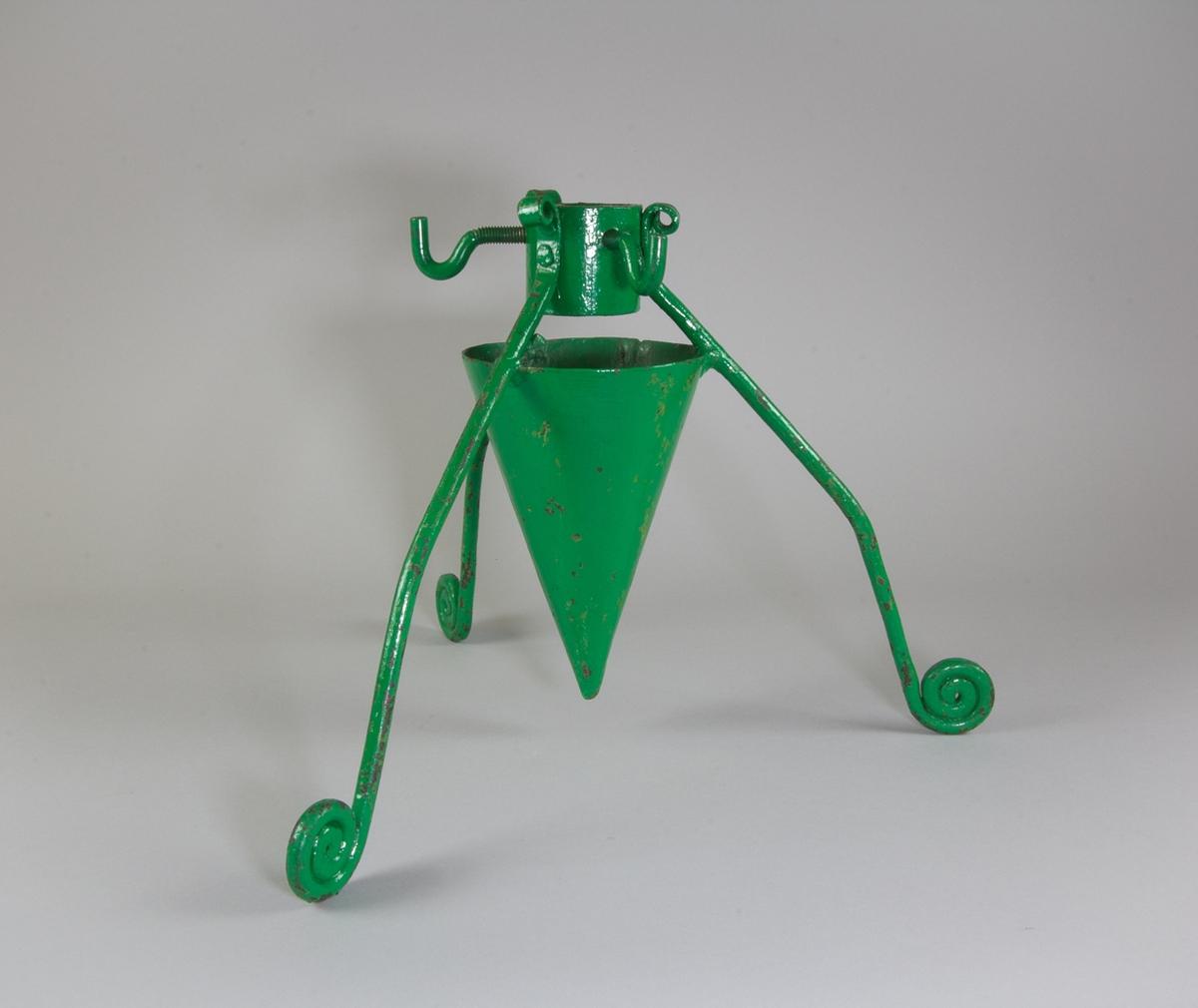 Julgransfot i grönmålad metall. Tre ben bestående av dekorativt böjda bandjärn. Konformad vattenbehållare i plåt, ring och skruvar med krokformade huvuden för fästande av granen.