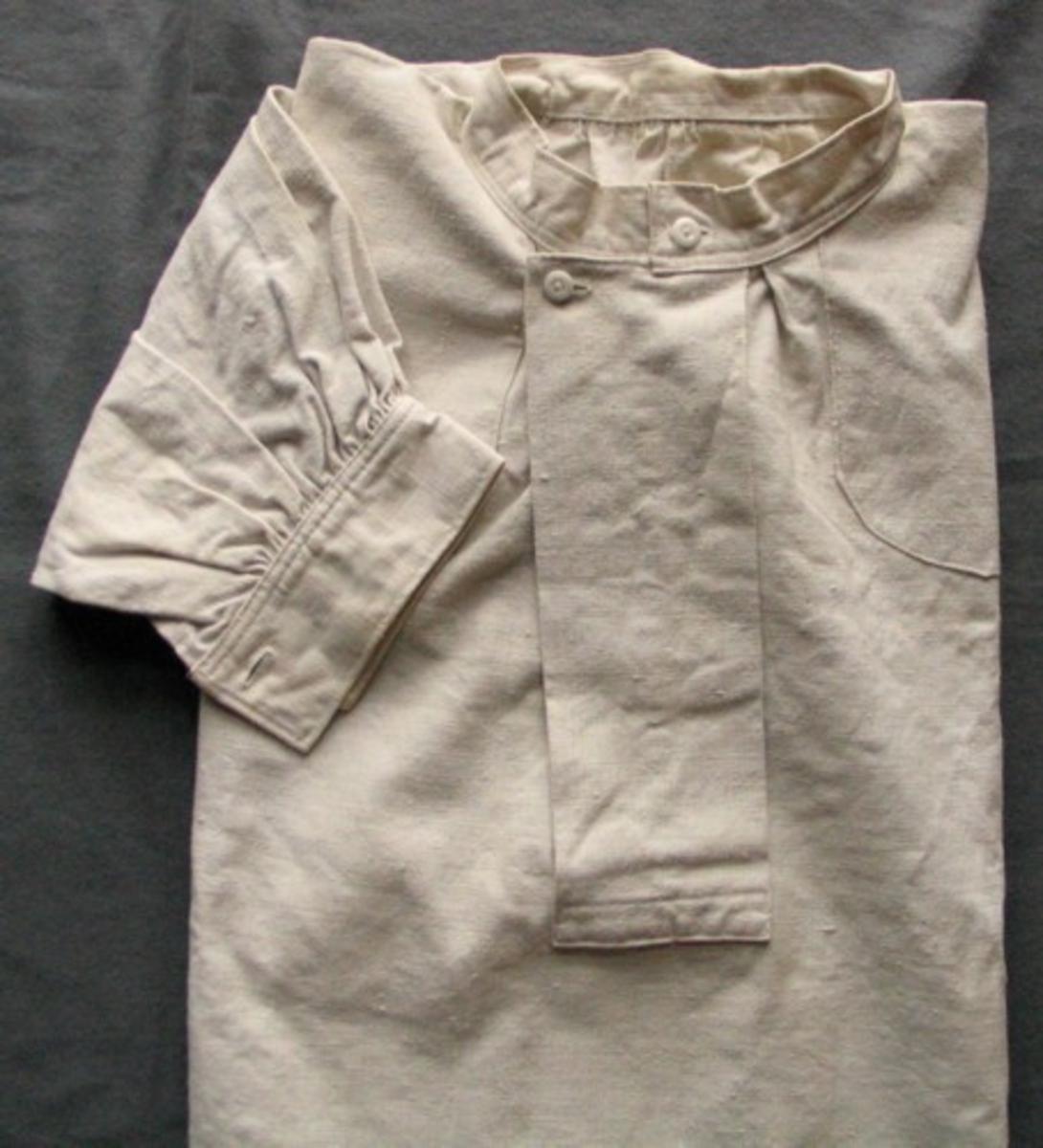 """Maskinsydd mansskjorta, oanvänd. Liten krage, 3 cm. Förstärkt med dubbelt tyg över axlarna. Ärmen är isydd med två lagda veck fram och två bak på axeln. 4,7 cm manchett, ärmsprund 7 cm. 2 vita porslinsknappar i halsen och för att förslaget, samt en på varje manchett. Handsydda knapphål. Sprund nertill i sidorna, 19,5 cm.  Enligt pånålad lapp: """"Skjorta sydd vid sekelskiftet på maskin efter gammal förebild""""."""