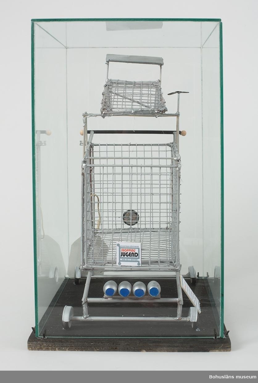 """Objekt i monter. Monter bestående av svartmålad platta sammanfogad av fem tunna plywoodskivor samt glashuv. Inuti montern finns ett objekt format som en kundvagn. Material: Glas, trä, metallnät, metallrör, plast, kartong, papper, snöre samt lim. Montern är en del av verket, ett slags """"viktighetssymbol"""", uppger Lars R Melander. Delarna mestadels målade med en grå """"aluminiumliknande"""" färg samt blå detaljer. Tre skyltar/etiketter med text: 1. SHOPPING JUGEND EXTRAVAGANZA 900 LADIES EDITION LTD Helt enkelt allt: spoiler, takbox, TV- antenn, drag, extraljus och farthållare. (Skylt limmad snett mot monterplatta.) 2. UDDEVALLA KÖPSTADEN SHOPPING JUGEND IKEA 2013 EDITION (Skylt fastlimmad mot metallnätet.) 3. Text som på 2. på en hålad etikett hängande i snöre fastknutet i objektet.  Bilagepärmen:  Information om Lars R Melanders utställning i X-galleriet, Konsthallen Trollhättan 24 augusti - 13 oktober 2013. Kopia av presentation i Nyheter P4 Väst / Sveriges Radio 2006-12-11 """"Bilderna som Bohusläningen stoppade""""."""