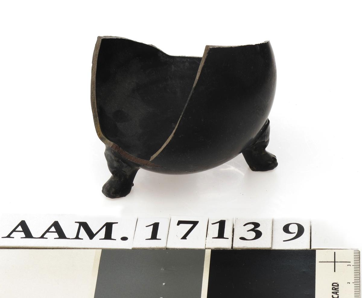 """Bunn og sideskår av tekanne, tidlig  Whieldon Wedgwood ware. produsert ca.  1755 - 1758 i """"Egyptian black"""".    a) Mørkebrunt gods, sort glasur. Flat bunnflate, midtstykket uten glasur. Tre korte buede ben. det ene avslått. Litt av rundet  side.    b) Litt avrundet side. H.5.7 B.7,3   De to delene a og b er sammenlimt på museet."""