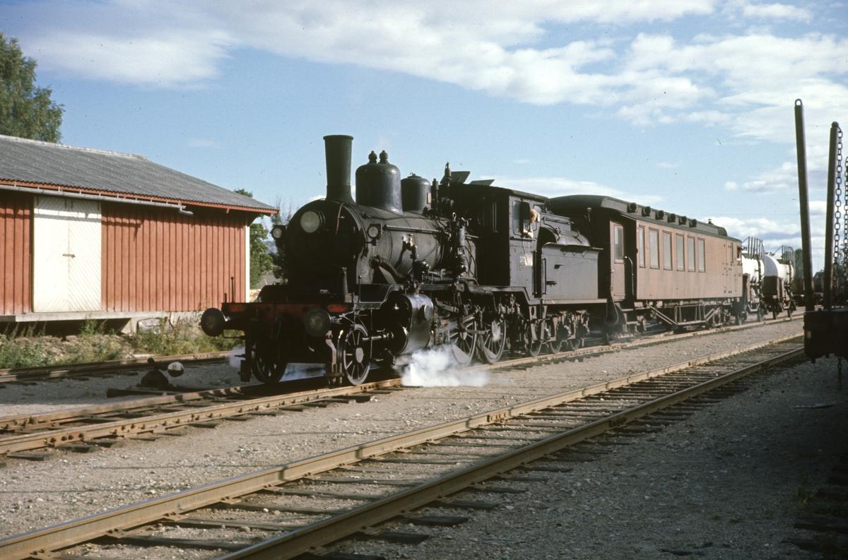 Skifting med godstog på Kirkenær stasjon på Solørbanen, trukket av damplok 21c nr. 377. En kombinert konduktør- og passasjervogn medfølger toget.