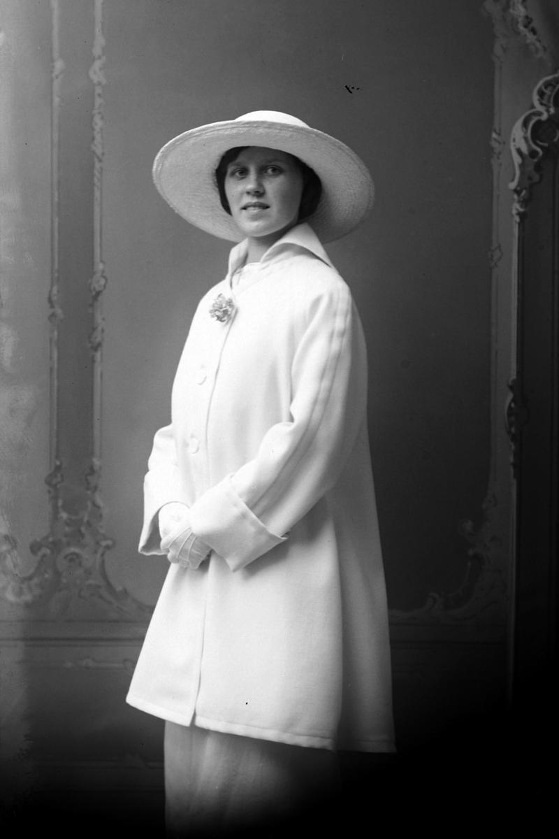 Studioportrett av en kvinne med en stor hvit hatt på hodet.