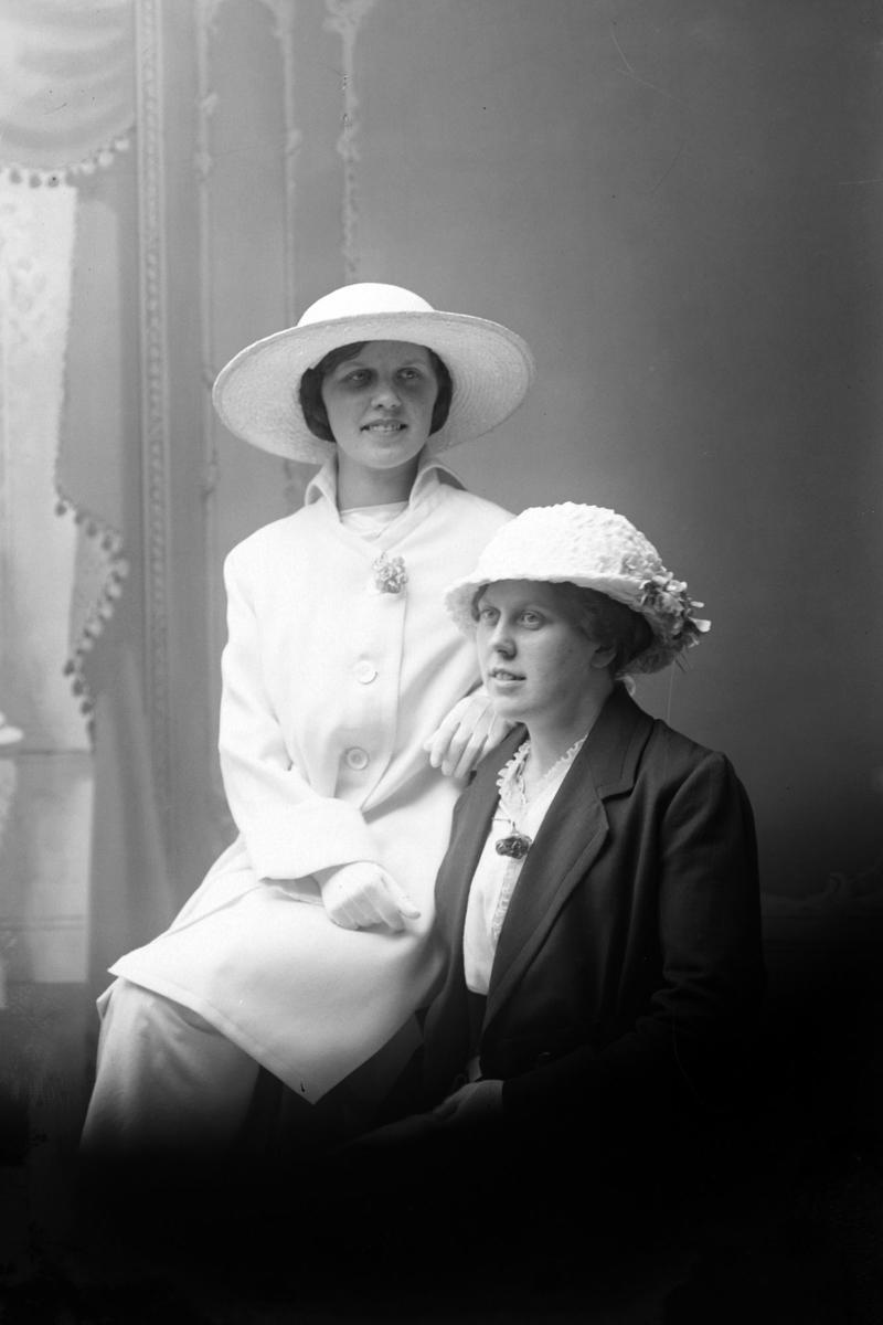 Studioportrett av to kvinner med hatter på hodet.