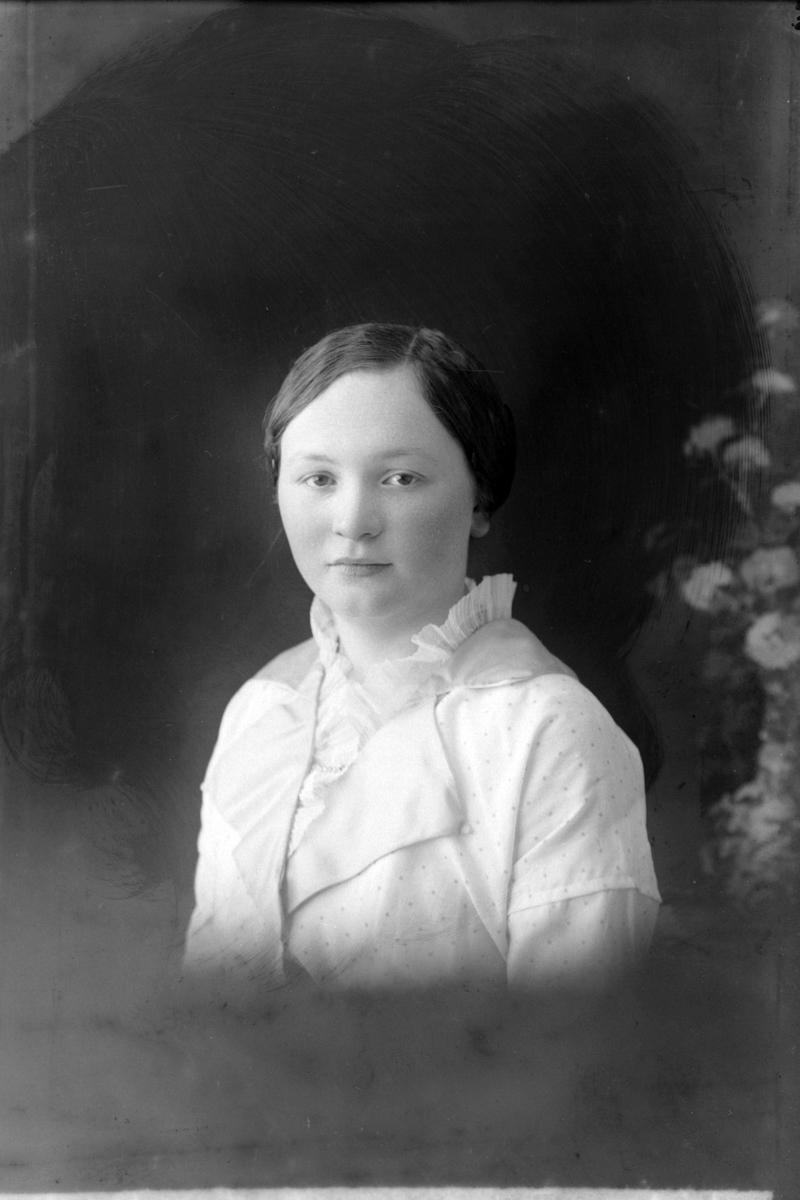 Studioportrett i halvfigur av en kvinne.