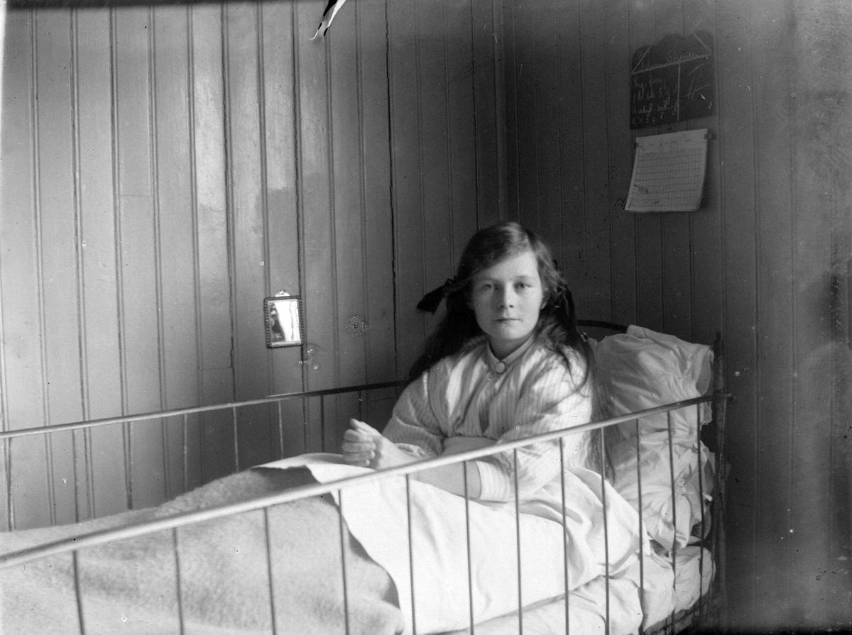 Bilde av en ung jente i sykehusseng.