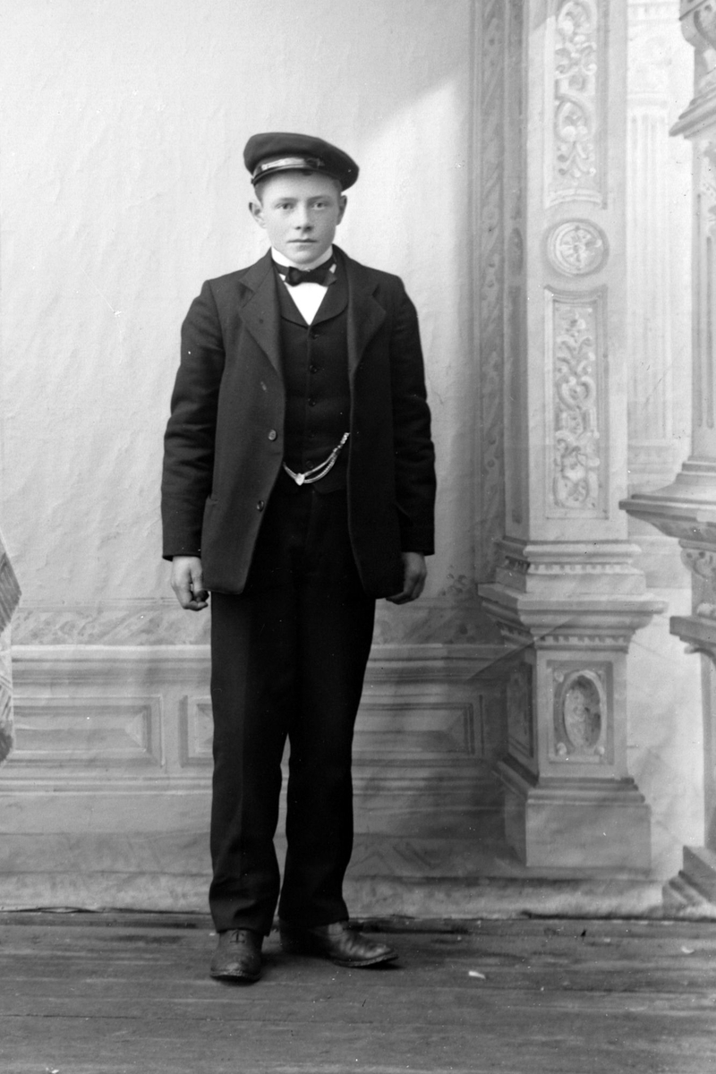 Studioportrett av en gutt i helfigur, muligens Arnold Simonsen.