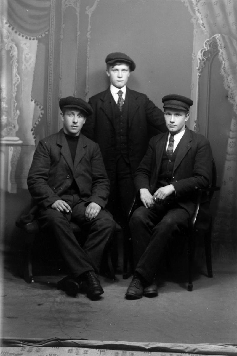 Studioportrett av tre unge menn.