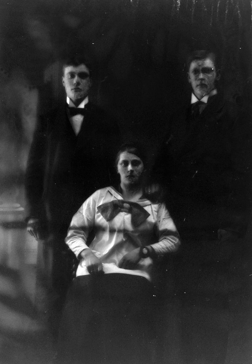 Studioportrett av to stående menn og en sittende kvinne.