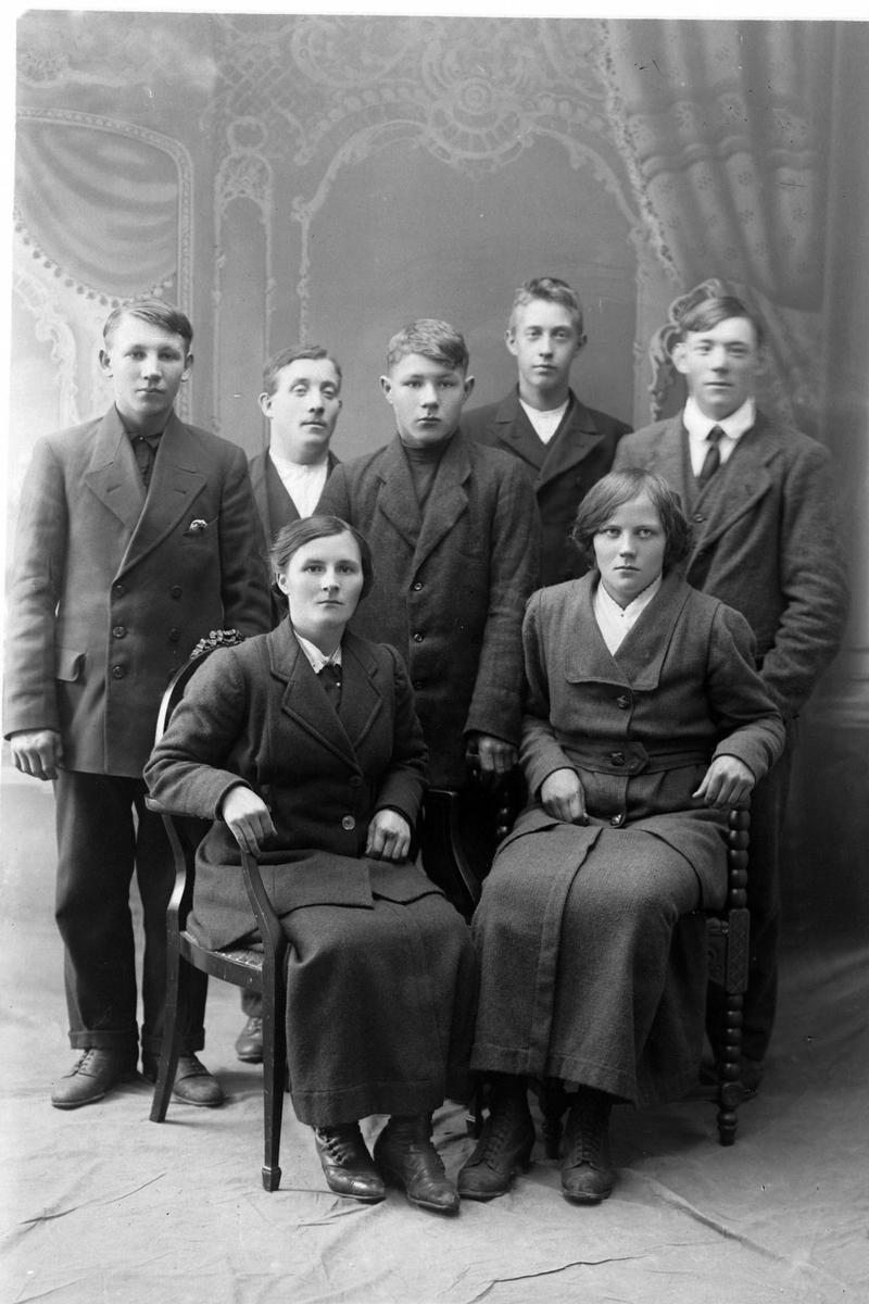 Studioportrett av en gruppe på syv personer.