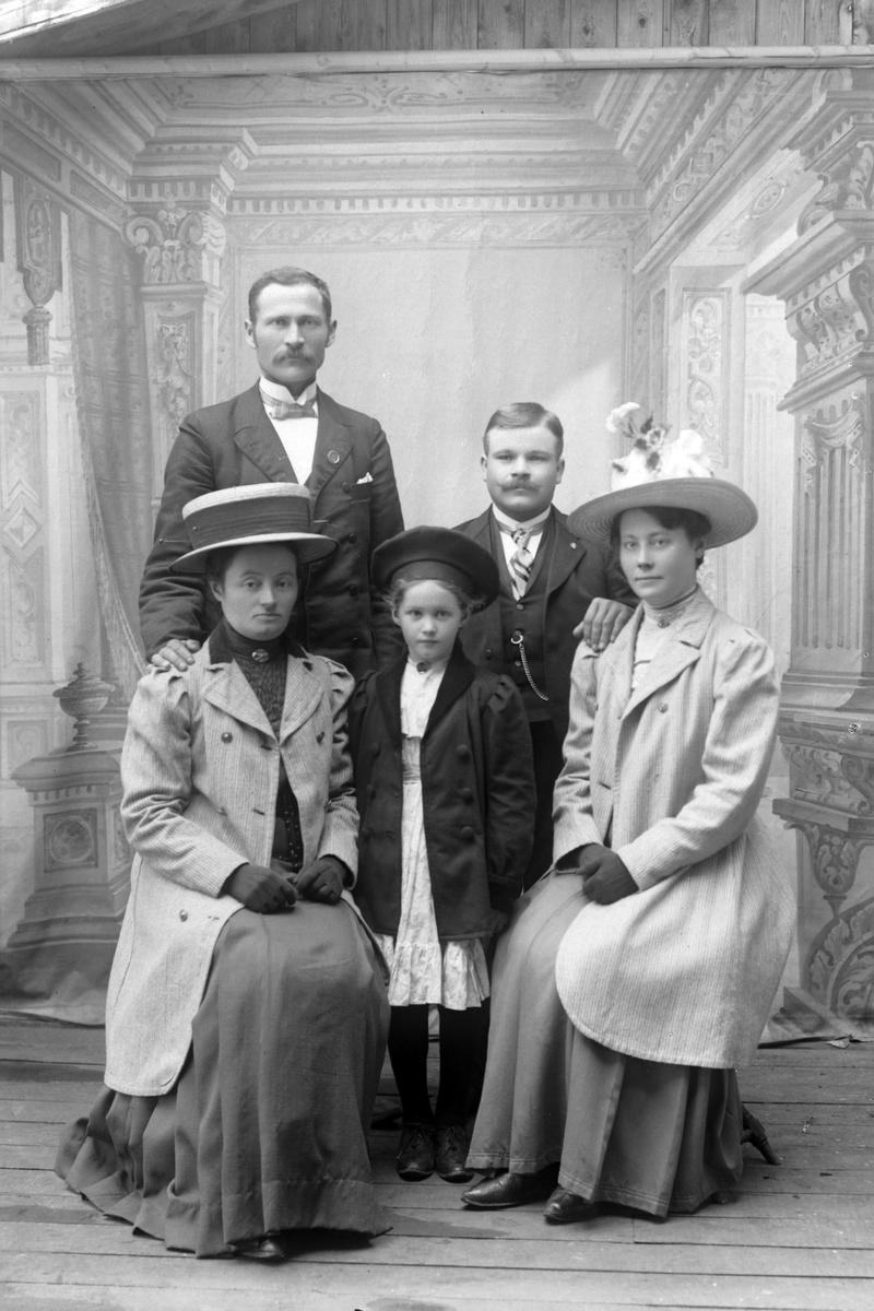 Studioportrett av fem personer i helfigur.