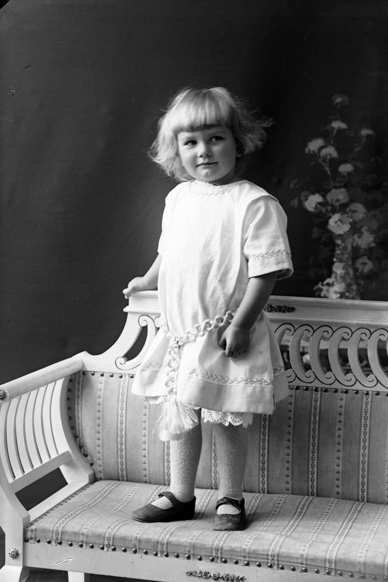 Studioportrett av en liten jente i hvit kjole.