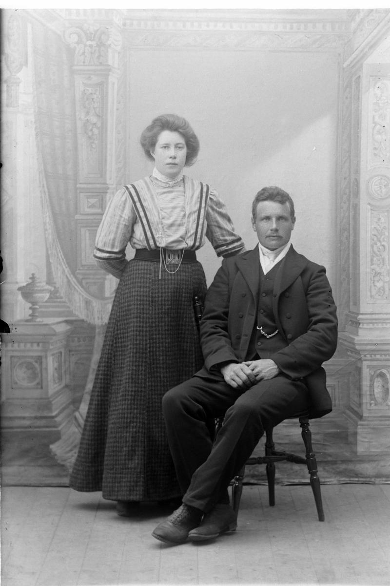 Studioportrett av en kvinne som står ved siden av en mann som sitter.