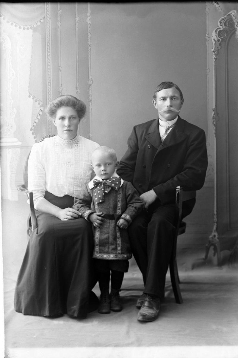 Studioportrett av en mann og kvinne med et barn imellom seg.