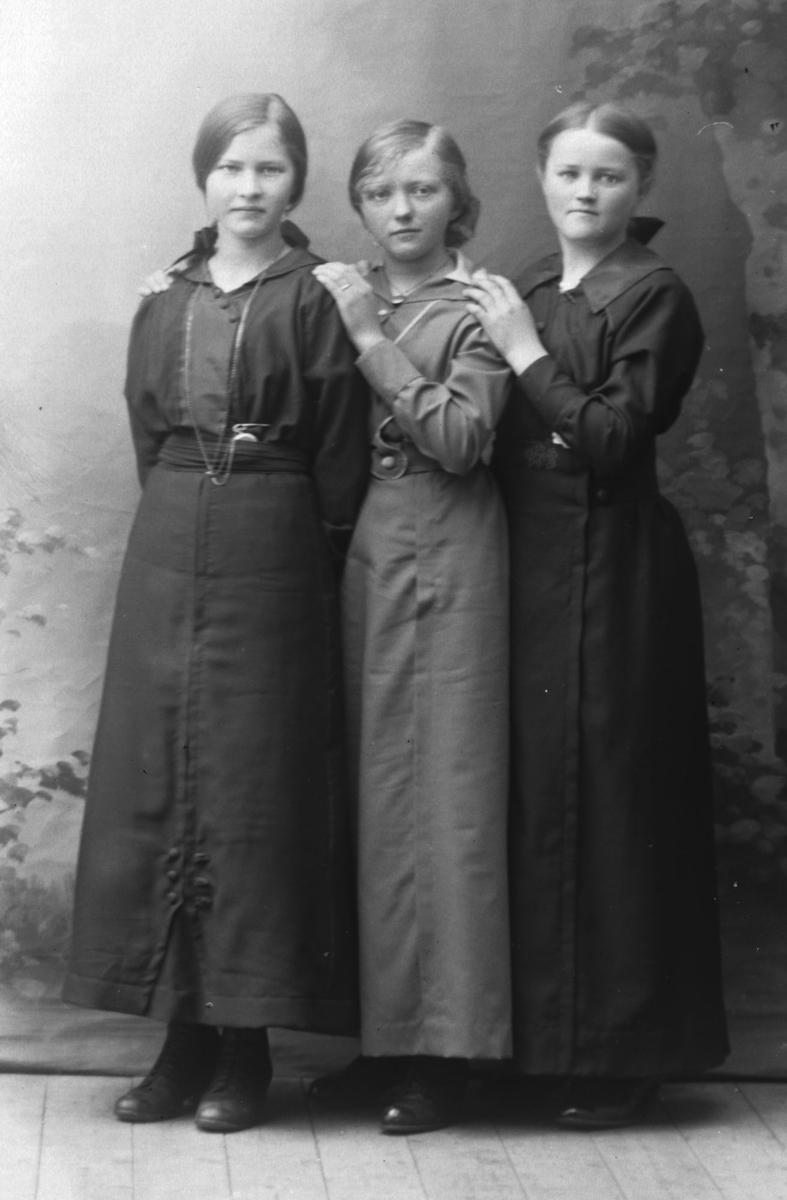 Studioportrett av tre unge piker i helfigur.