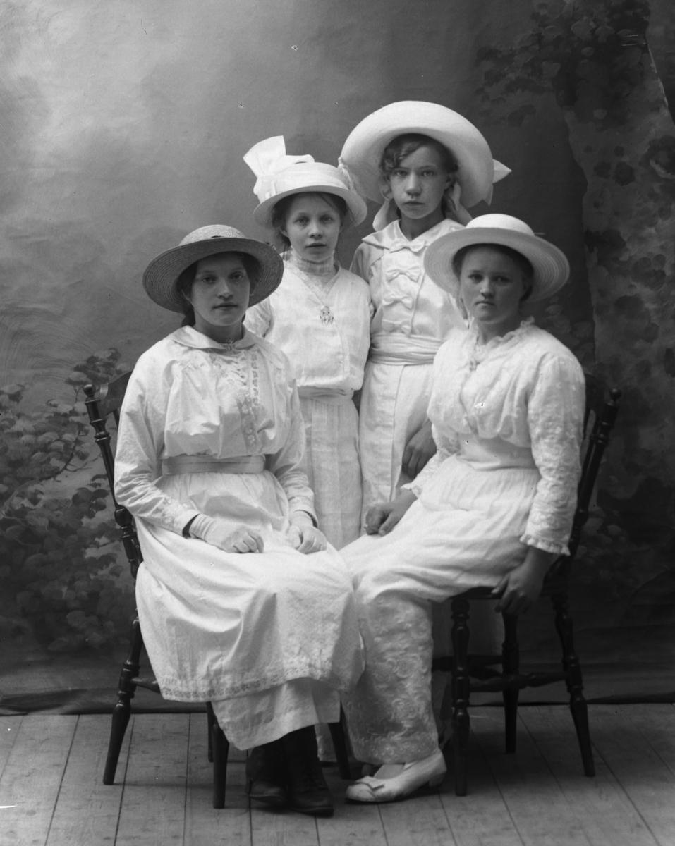 Studioportrett av fire unge kvinner i helfigur.