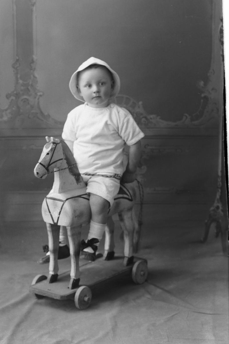 Studioportrett av en liten gutt på en gyngehest.