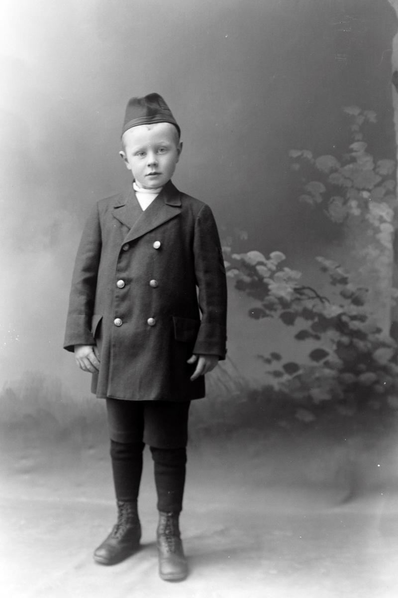 Studioportrett av en ung gutt i helfigur.