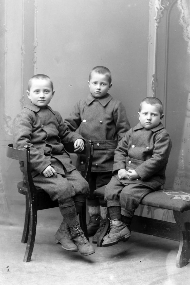 Studioportrett av tre unge gutter.
