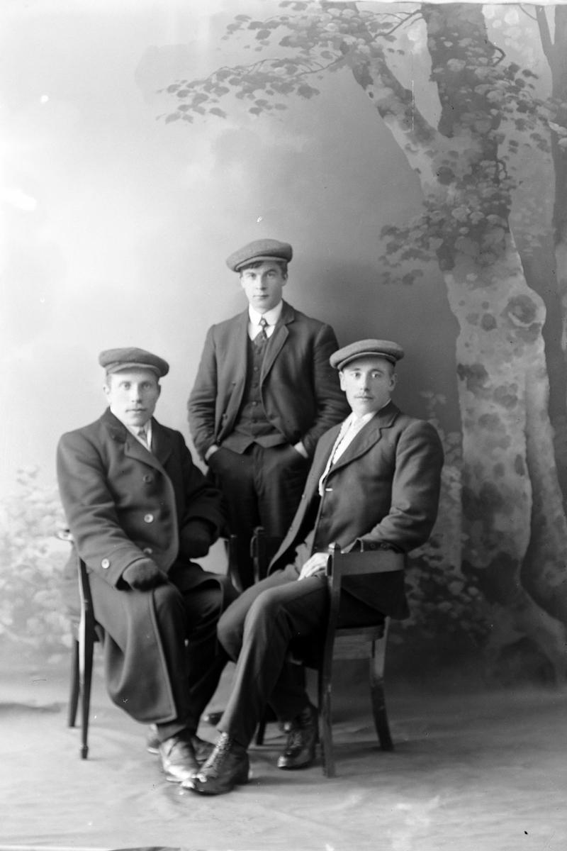 Studioportrett av tre menn med luer.