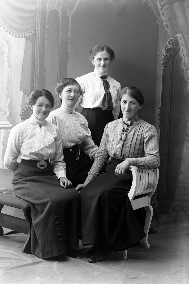 Studioportrett av tre kvinner sittende foran én som står.