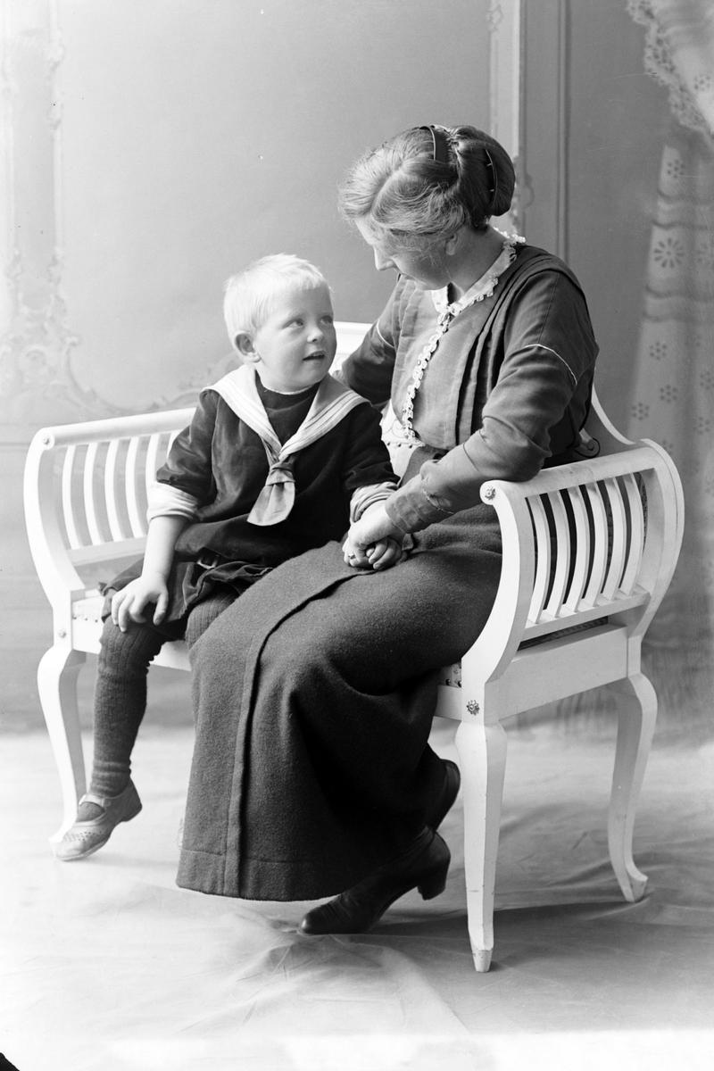 Studioportrett av en kvinne sittende ved siden av en gutt.