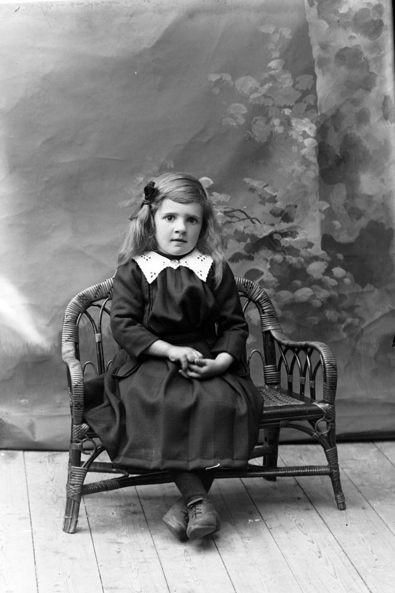 Studioportrett av en ung pike sittende på en benk.