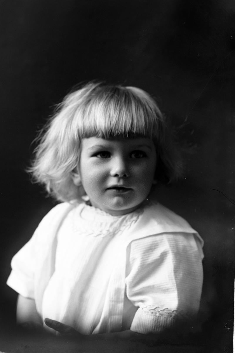 Studioportrett i halvfigur av en liten jente.
