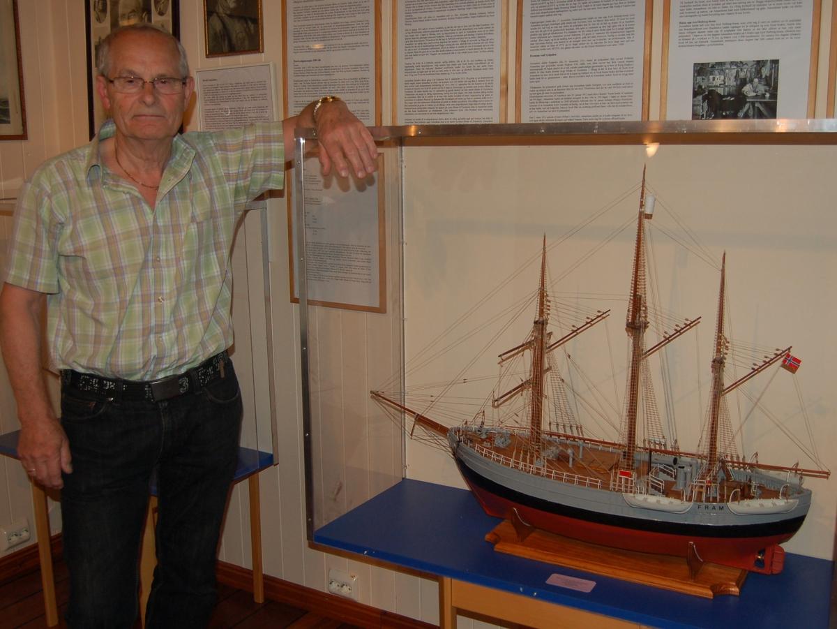 """Modellbyggeren fotografert på Ishavsmuseet Aarvak ved siden av modellen han har bygt. Modellen er av polarskipet """"Fram"""", og i målestokk 1:50 etter tegninger fra Norsk Sjøfartsmuseum."""