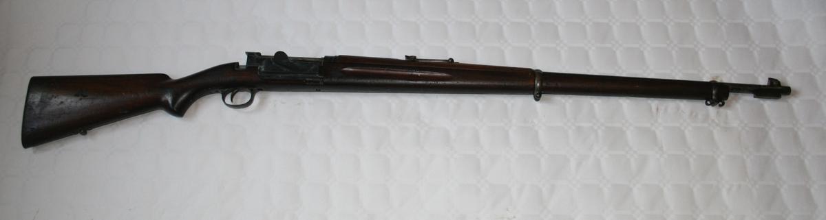Geværet er en Krag Jørgensen med magasin til 5 patroner. Løpet er utstyrt med feste for bajonett, og i enden av kolben er det en luke til et sylindrisk hulrom i kolben på 1,85x20 cm.