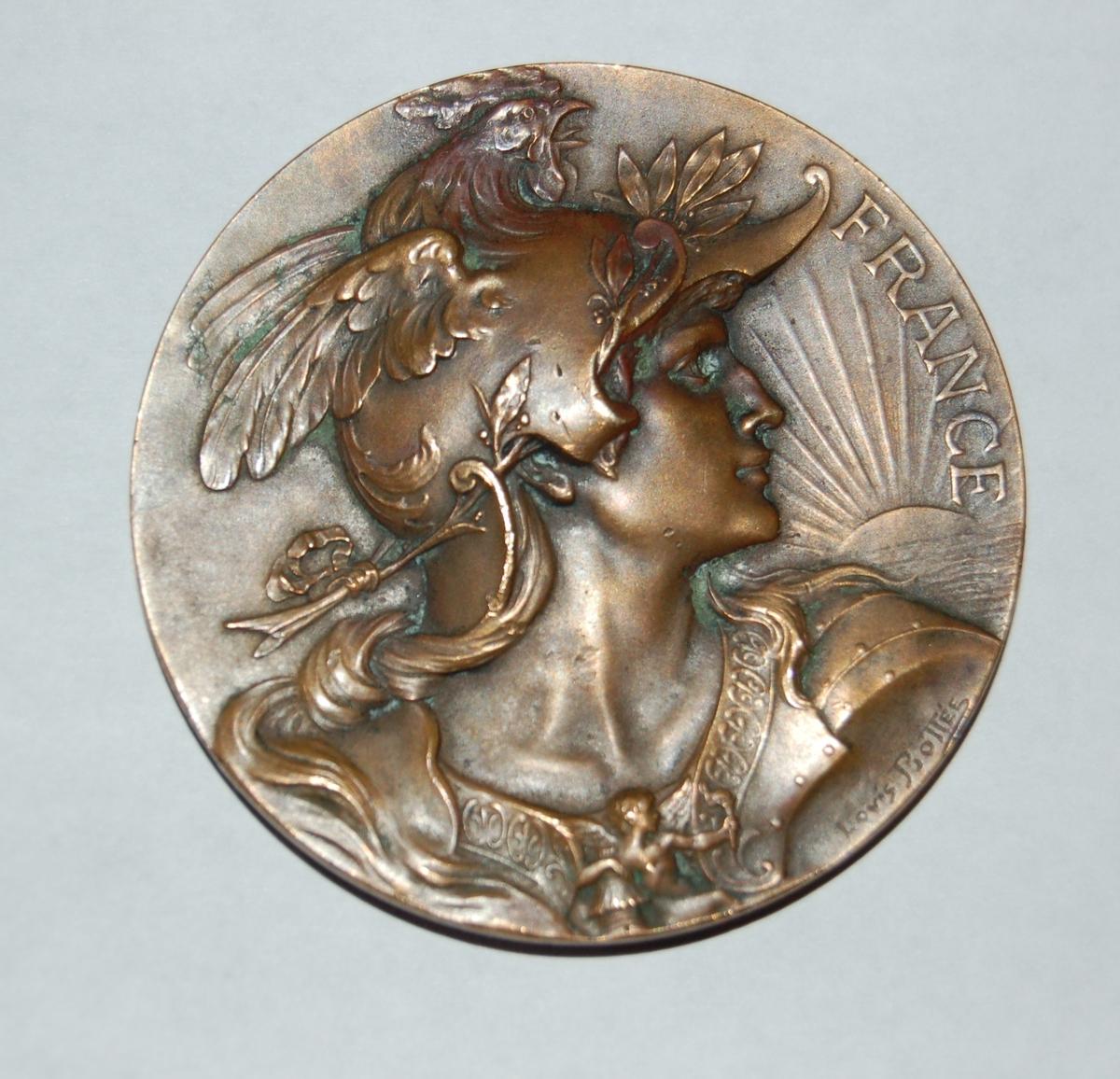 På forsiden er det eit portrett av truleg ein helgen e.l., og ordet FRANCE På baksiden er det en kvinnefigur som holder i enden av en rosenkrans som omgir en sirkelplate med medaljens formål nedskrevet, og kven den er dedikert til.
