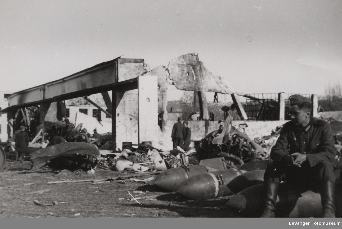 Betonghangar på Værnes ødelagt av britiske bombefly. To Junkers stjernemotorer ligger ved siden av bombene soldatene sitter på.