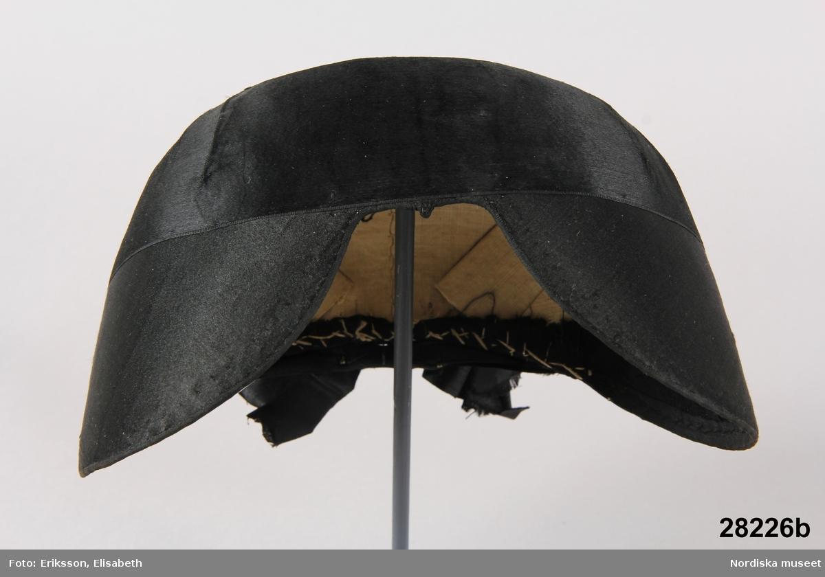 """A. Bindmössa lokalt """"tvåstycksmössa""""  från öra till öra 37 cm. Sydd av 2 delar av svart sidentaft, omönstrad och försedd med ett enfärgat svart sidenmoiréband kring kullen, avslutat med utvikta och uddklippta flikar. Foder av oblekt linnelärft. Berit Eldvik 2004"""