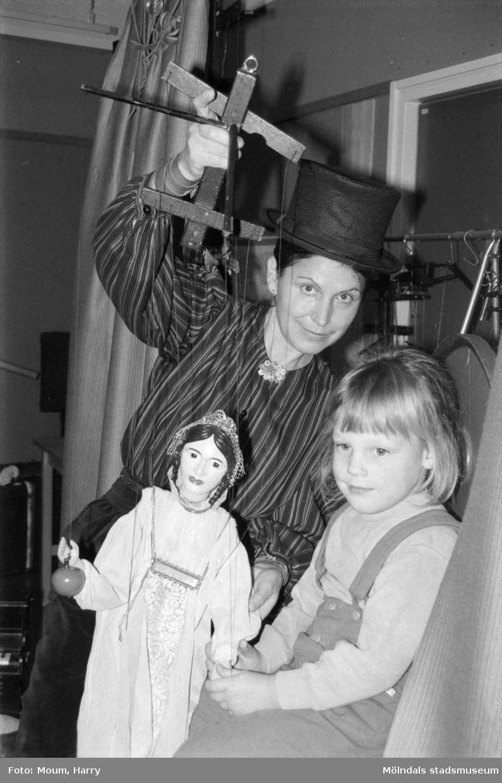 """Familjesöndag med diverse aktiviteter på Almåsgården i Lindome, år 1984. """"Eliška Recinovà fick hjälp av Anna Erlandsson att ställa i ordning inför marionettföreställningen.""""  För mer information om bilden se under tilläggsinformation."""