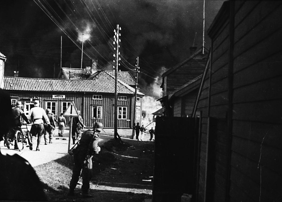 Bildet er tatt i Vadsø under 2. verdenskrig. Det viser det som på folkemunne kalles 'Storbombinga', 23. august 1944. bildet er tatt i sentrum i Vadsø i Nyborgveien. Til venstre i bildet ser vi apoteket. En flokk tyske soldater er på vei mot nedslagsstedet til en bombe. Vi ser røyken etter bombenedslaget bak apoteket. Himmelen er svart av røyk. I tekst til bildet står det at Kirsten Bergh bodde i Frelsesarmeen sitt hus som ses helt til venstre